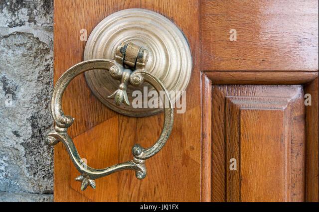 Closeup of antique copper ornate door knocker over an aged wooden door, Eyup Sultan Mosque, Istanbul, Turkey - Stock Image