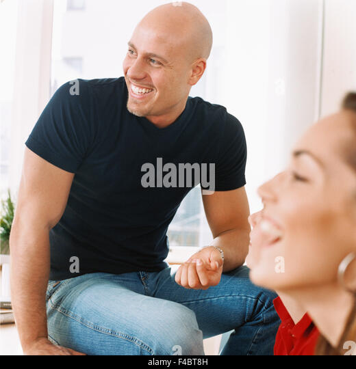 bald headed color image happy indoors laughing man optimism positive several shaved head sitting woman - Stock-Bilder