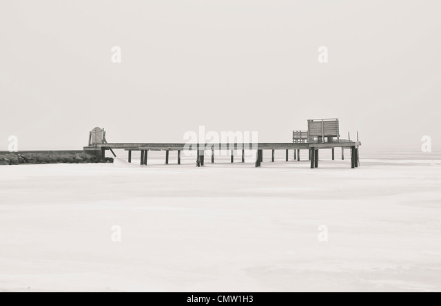 Pier in snow covered sea - Stock Image