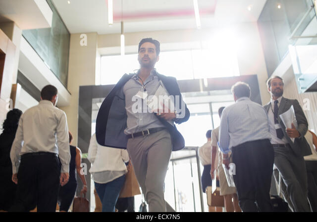 Men holding documents and running in office corridor - Stock Image