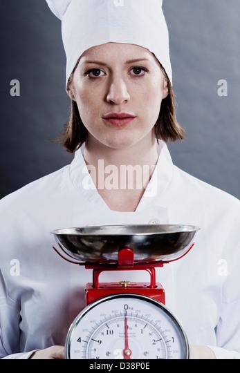 Chef holding kitchen scales - Stock-Bilder