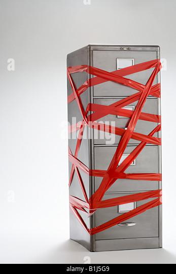 Red tape over filing cabinet - Stock-Bilder