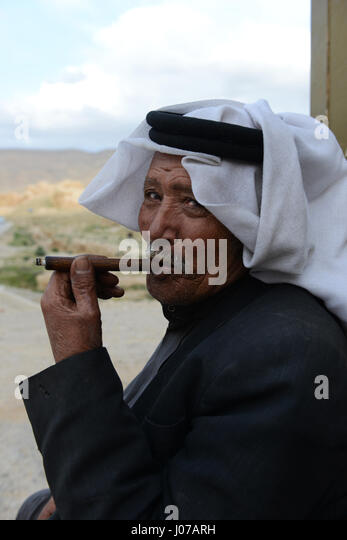 A Bedouin man smoking his cigarette. - Stock Image