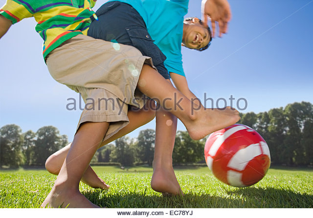 Smiling boys playing soccer in park - Stock Image