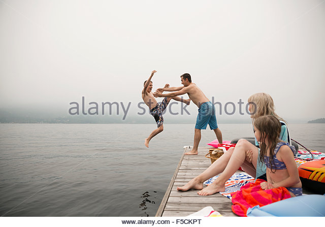Playful father throwing son into lake from dock - Stock Image