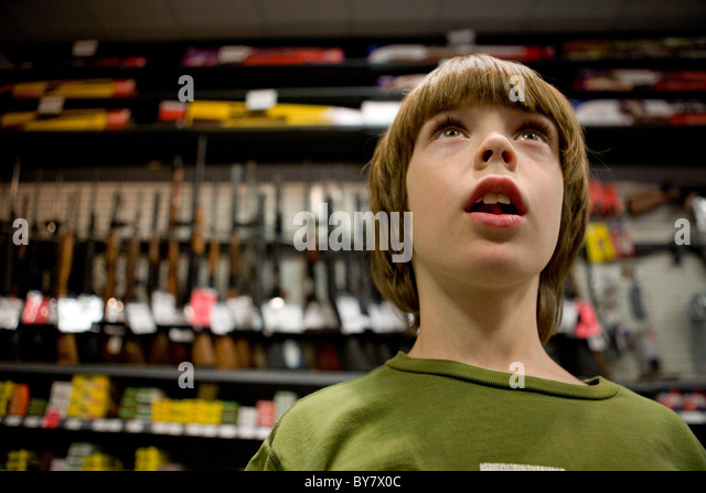 Child standing in front of a wall of guns for sale. - Stock Image