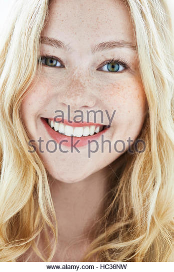Portrait of young woman with blonde hair, smiling. - Stock Image