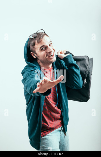 Ecstatic man in hoodie traveling with luggage. - Stock Image