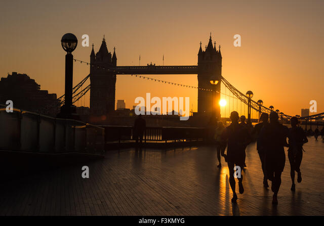 UK weather, London, 9th October 2015. Joggers enjoy their early morning exercise as Tower Bridge is silhouetted - Stock-Bilder