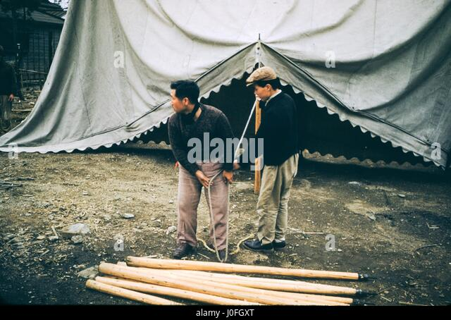 Two Japanese men pause in their work while erecting a tent, using rope and bamboo poles, 1952. - Stock Image