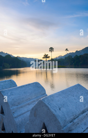 Kandy Lake at sunrise, the island of the Royal Summer House, with the Clouds Wall in the foreground, Kandy, Sri - Stock Image