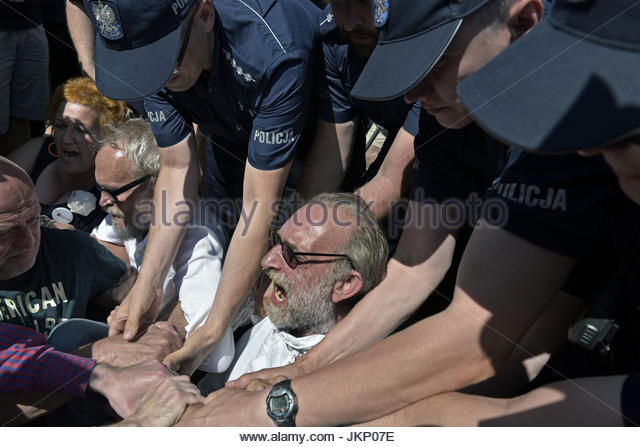Warsaw, Poland. 24th July, 2017. Police hold down protesters during a peaceful demonstration in the Polish capital - Stock Image