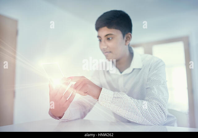 Fiji Indian boy texting on glowing cell phone - Stock-Bilder