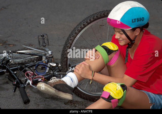 New Jersey Plainfield Asian teen bicycle accident injury pain leg helmet holding - Stock Image