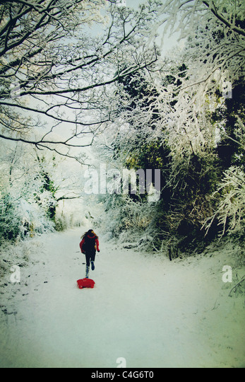 girl running in the snow with sledge - Stock-Bilder