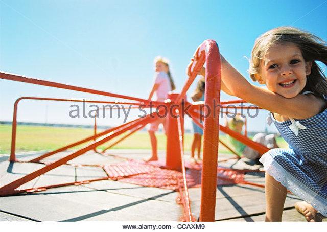 Children riding on playground merry-go-round - Stock-Bilder