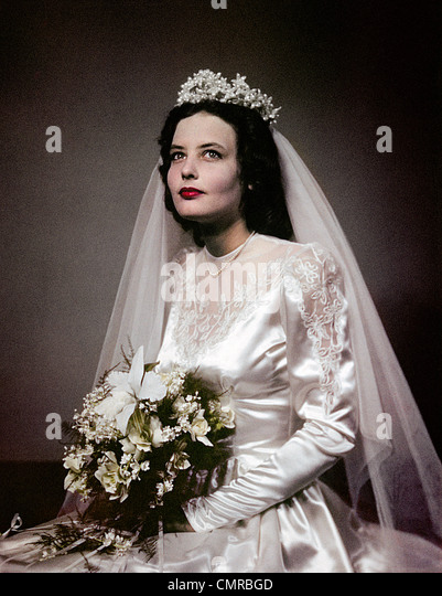 1940s 1950s PORTRAIT BRUNETTE BRIDE IN BRIDAL GOWN WITH FLOWER BOUQUET - Stock Image