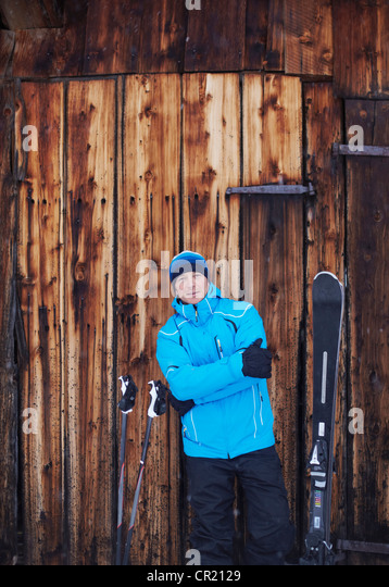 Man standing with skis and poles - Stock Image