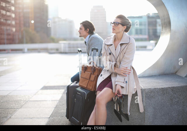 Businessman and woman waiting on city rooftop parking lot - Stock Image