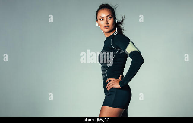 Portrait of fit young woman listening to music on earphones. Healthy muscular woman with arm band over grey background. - Stock Image