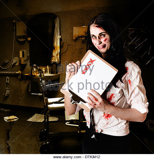 Chilling zombie nurse standing in decrepit hospital with unhealthy checklist in a depiction of bad health - Stock Image