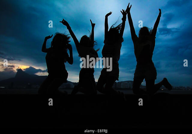 Silhouette of four women jumping in the air - Stock Image