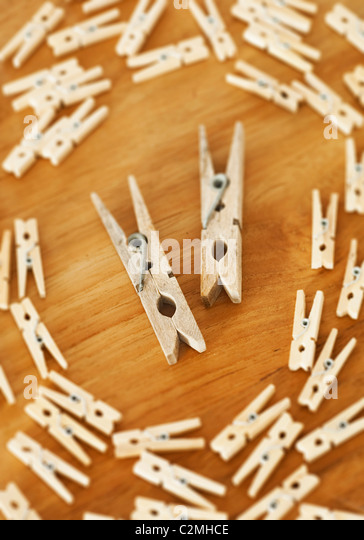 Two Large Clothespins Surrounded By Smaller Ones - Stock Image