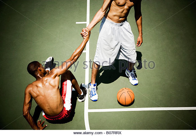 Two men playing on an outdoor basketball court - Stock Image