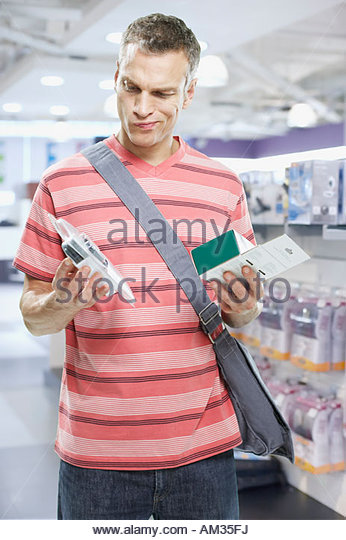 Man looking at electronics in store - Stock Image