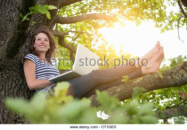 Smiling woman using laptop in tree - Stock-Bilder