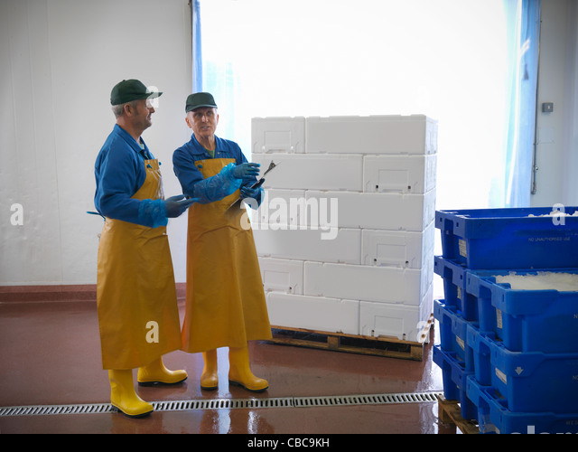 Workers with pallets in warehouse - Stock Image