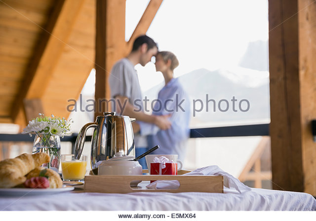 Breakfast on bed with couple in background - Stock-Bilder