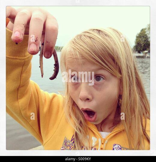 A girl's eyes light up while looking at a squirmy crawly worn. - Stock-Bilder