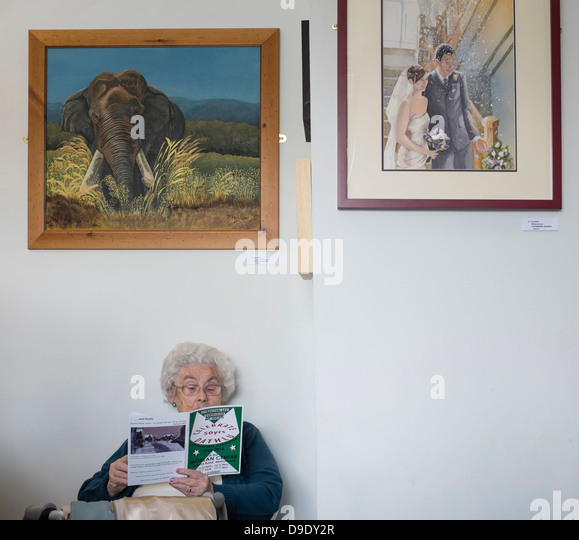 A woman reading the catalogue at the opening of an exhibition of amateur hobbyist 'sunday painter' paintings, - Stock-Bilder