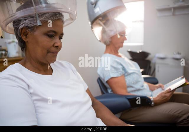Woman under hair dryer stock photos woman under hair for Reading beauty salon