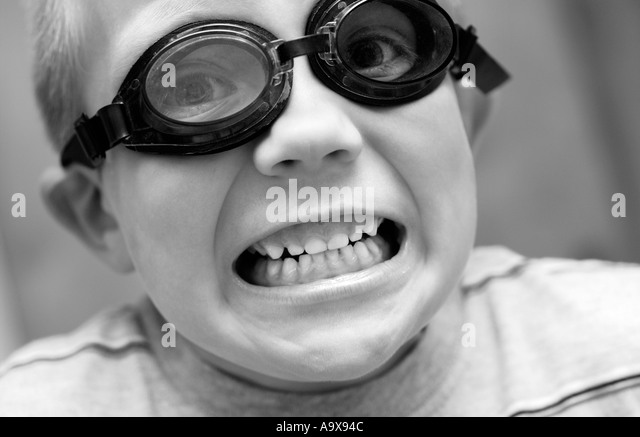 5 year old boy wearing goggles with mouth open - Stock Image