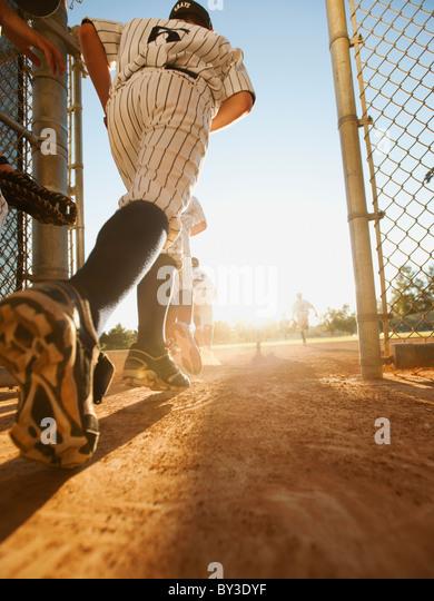 Baseball players (10-11) entering baseball diamond - Stock Image