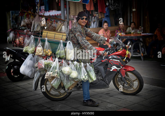 Thailand street food. Vendor selling and delivering food from his motorcycle. Southeast Asia - Stock Image