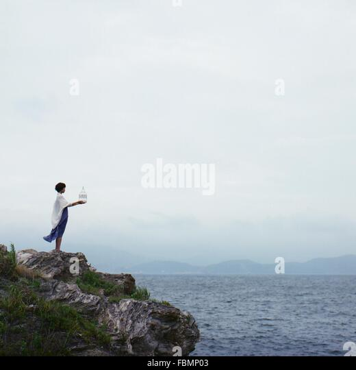Female Standing On Rock Shore, Holding Pot, Looking At Seascape, Wind Blowing - Stock Image