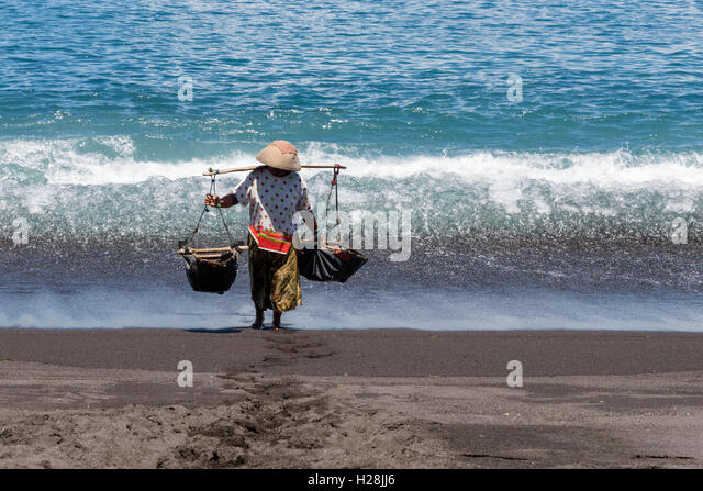 Woman carrying a teku-teku to collect sea water that later will be splashed on the sand to extract the salt. - Stock-Bilder