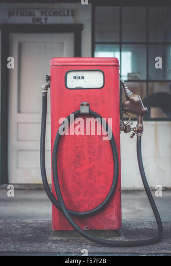 An old fashioned red gas pump sits outside a closed down fueling station. - Stock Image