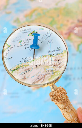 Blue tack on map of Africa with magnifying glass looking in on Algiers, Algeria - Stock Image
