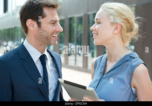 Real estate agent with digital tablet meeting with potential buyer - Stock Image