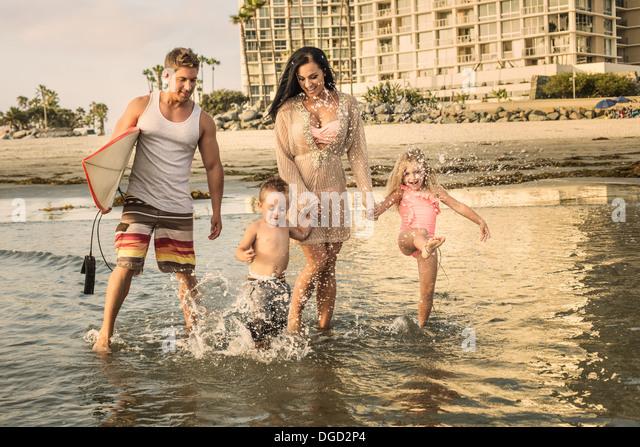 Young family paddling through water - Stock-Bilder
