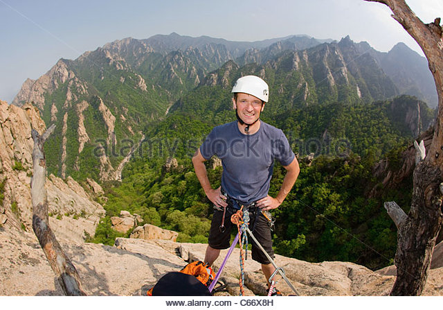Climber standing on rocky mountain - Stock Image