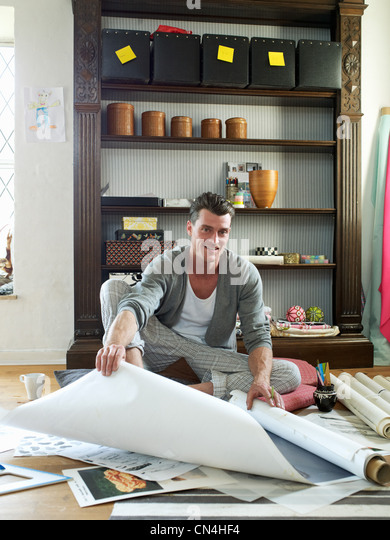 Mid adult man looking at sketches and artwork on floor, portrait - Stock Image