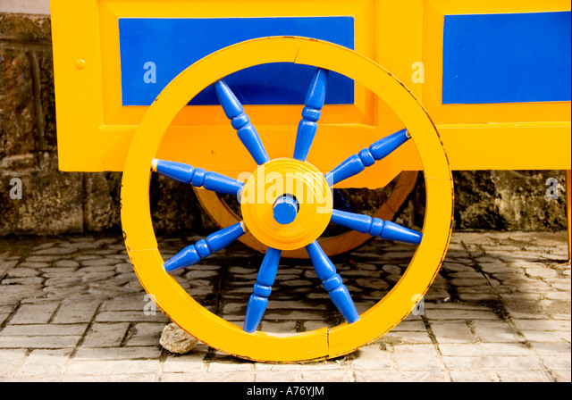Cozumel Mexico San Miguel town colorful cart wheel bright yellow and blue - Stock Image