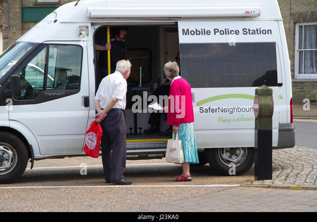 Two seniors speak with PCSOs in a mobile police station - Stock Image