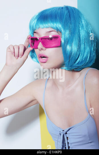 Individuality. Woman wears Blue Glossy Wig and Pink Glasses - Stock Image