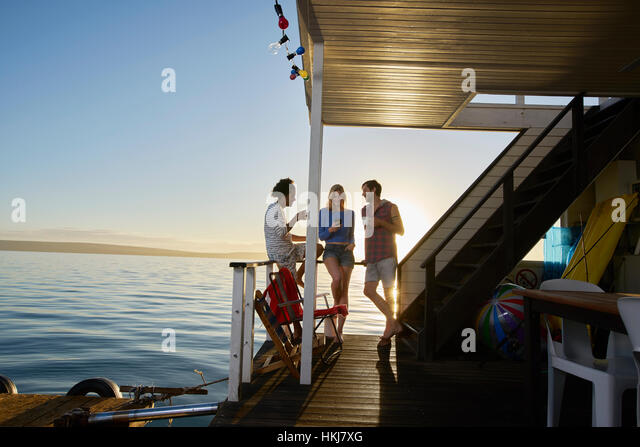 Young adult friends hanging out on summer houseboat on ocean - Stock-Bilder